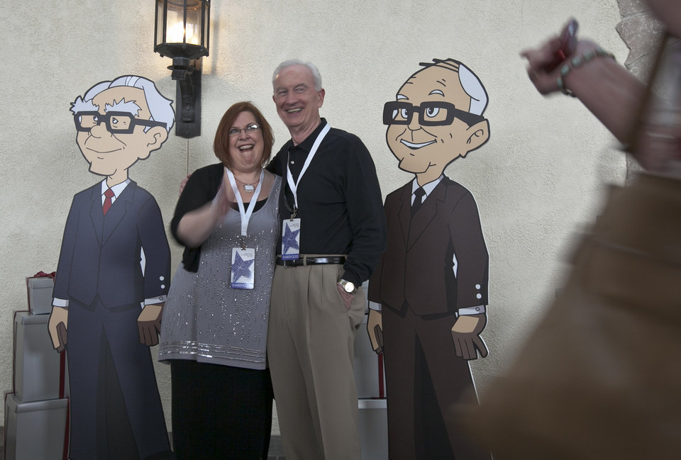 Photo -   Shareholders pose with cardboard cartoons of Berkshire Hathaway chairman and CEO Warren Buffett, left, and his vice chairman Charlie Munger outside the Berkshire-owned Borsheims jewelry store in Omaha, Neb., Friday, May 4, 2012. Berkshire Hathaway is expected to have 30,000 shareholders come to Omaha for it's annual shareholders meeting this weekend. (AP Photo/Nati Harnik)