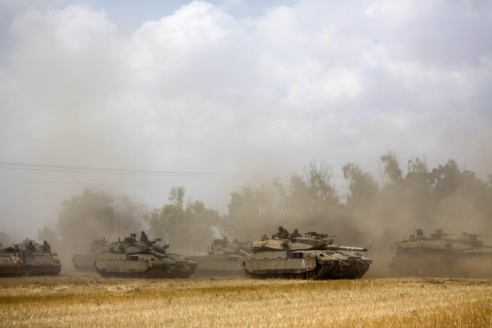 Photo - Israeli armor is seen through dust near the Israel and Gaza border, Saturday, July 19, 2014. Israel pounded Hamas rocket launchers, uncovered more than a dozen cross-border tunnels and engaged in gunbattles with Palestinian militants Saturday, as fighting intensified on the second day of its open-ended ground operation in Gaza, as the Palestinian death toll continued to rise. (AP Photo/Dusan Vranic)