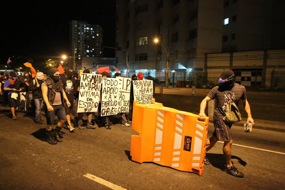 Photo - Anti-World Cup demonstrators walk toward Maracana stadium to protest the money spent on the World Cup soccer tournament and demand better public services in Rio de Janeiro, Brazil, Sunday, June 15, 2014. Police clashed with protesters marching toward the stadium ahead of the match between Argentina and Bosnia. (AP Photo/Leo Correa)