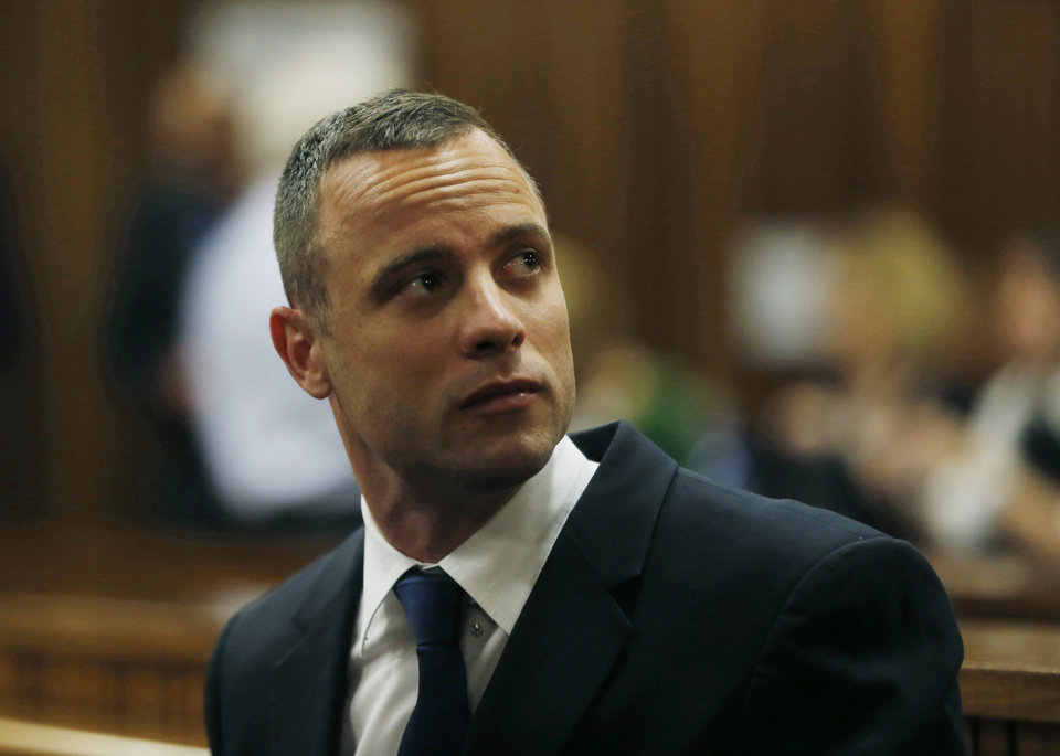 Photo - Oscar Pistorius is seated in a courtroom at the high court in Pretoria, South Africa, Tuesday, May 6, 2014. A man who lives next to the house where Pistorius fatally shot his girlfriend has testified at the athlete's murder trial about the night of the killing, saying he heard a man crying loudly and that he called the security of the housing estate for help. (AP Photo/Mike Hutchings, Pool)