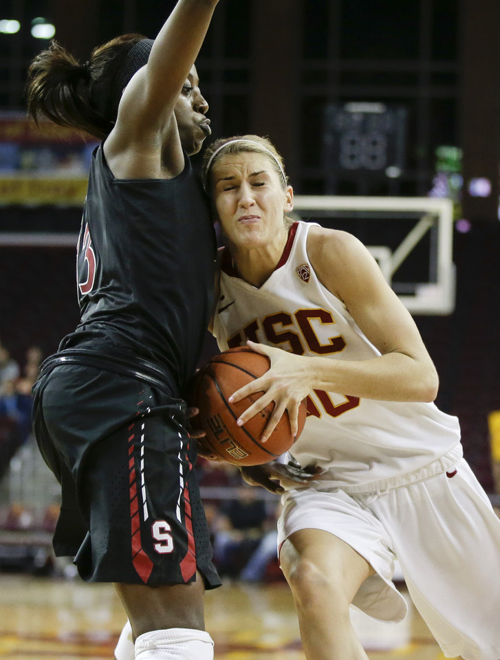 Photo - Southern California forward Christina Marinacci, right, tries to drive around Stanford forward Chiney Ogwumike during the second half of an NCAA women's basketball game in Los Angeles, Friday, Feb. 15, 2013. Stanford defeated Southern California 79-55 (AP Photo/Chris Carlson)