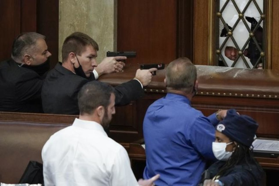 Photo -  U.S. Capitol Police with guns drawn watch as protesters try to break into the House Chamber at the U.S. Capitol on Wednesday. Oklahoma Rep. Markwayne Mullen, in the white shirt, later said he was tried to reason with the rioters. [AP Photo]