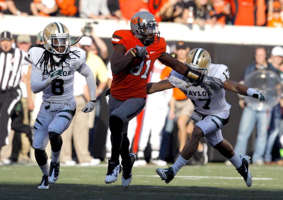 Photo - Oklahoma State's Justin Blackmon (81) tries to get by Baylor's K.J. Morton (8) and Mike Hicks (17) during a college football game between the Oklahoma State University Cowboys (OSU) and the Baylor University Bears (BU) at Boone Pickens Stadium in Stillwater, Okla., Saturday, Oct. 29, 2011. Photo by Sarah Phipps, The Oklahoman