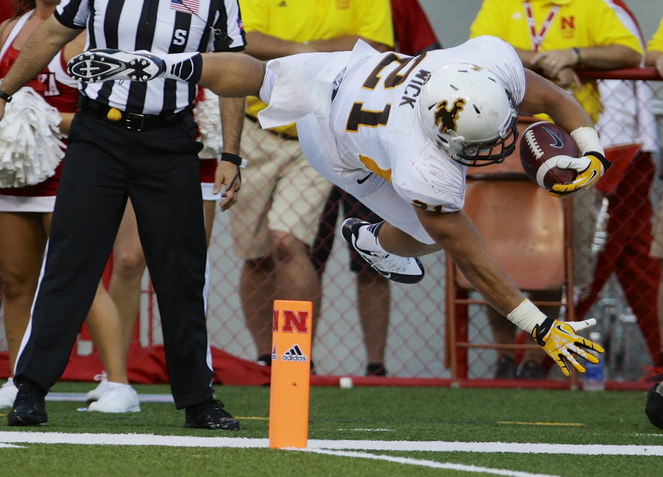 Photo - Wyoming running back Shaun Wick (21) leaps as he attempts a touchdown but steps out of bounds beforehand in the first half of an NCAA college football game against Nebraska in Lincoln, Neb., Saturday, Aug. 31, 2013. (AP Photo/Nati Harnik)