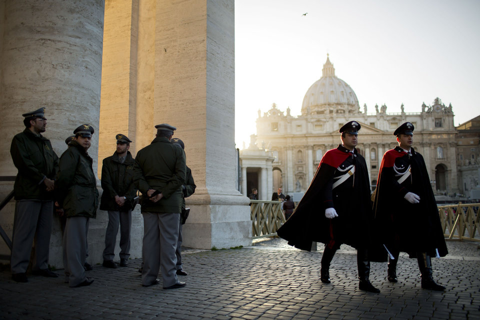 Photo - Security guards patrol in St. Peter's Square at the Vatican, Monday, March 18, 2013. a day before the inaugural Mass of Pope Francis.  The Vatican released details of the pope's installation Mass on Tuesday as well images of his coat of arms and fisherman's ring. In addition to more than 132 government delegations, the Vatican said 33 Christian delegations will be present, as well as representatives from Jewish, Muslim, Buddhist, Sikh and Jain communities. (AP Photo/Oded Balilty)