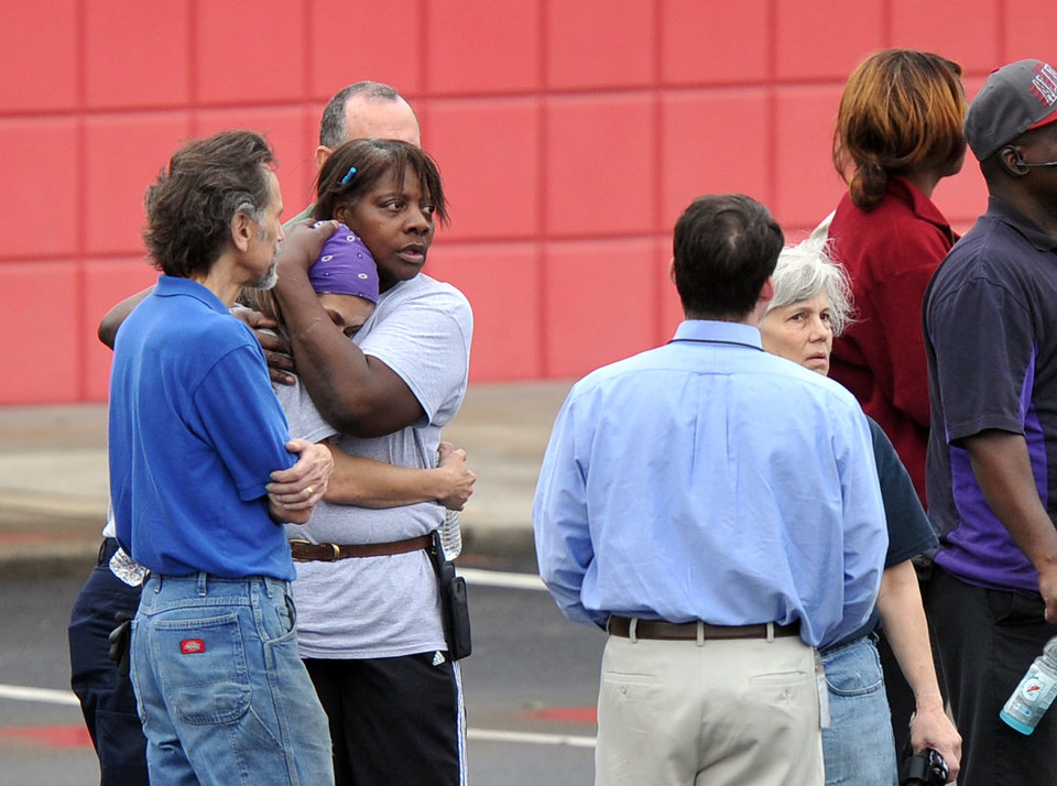 Photo - FedEx Employee Lisa Aiken, wearing bandana, is embraced by a co-worker as other FedEx employees gather at a skating rink following a shooting at a FedEx facility in Kennesaw, Ga., on Tuesday, April 29, 2014.  A shooter described as being armed with an assault rifle and having bullets strapped across his chest opened fire Tuesday morning at a FedEx station outside Atlanta, wounding at least six people before police found the suspect dead from an apparent self-inflicted gunshot.