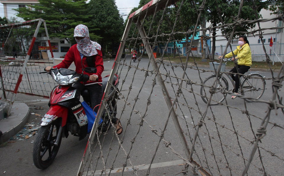 Photo - People drive past barbed-wire barricades at entrance of an industrial park in Binh Duong province, Vietnam Saturday, May 17, 2014, after mobs attacked foreign owned factories following anti-China protests. Vietnam's prime minister ordered an end Saturday to all