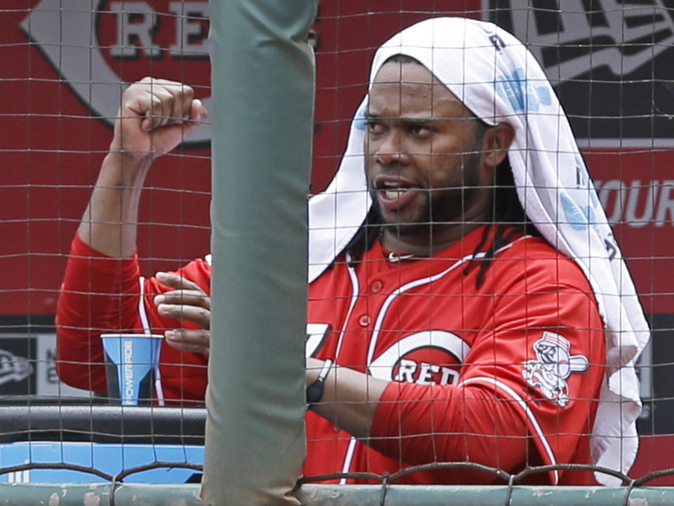 Photo - Cincinnati Reds starting pitcher Johnny Cueto clinches his fist in the dugout after relief pitcher Manny Parra got the final two outs in the seventh inning of a baseball game against the Chicago Cubs, Tuesday, July 8, 2014, in Cincinnati. Parra relieved Cueto in the seventh with the bases loaded and one out. Cueto earned his ninth win of the season as Cincinnati won 4-2. (AP Photo/Al Behrman)