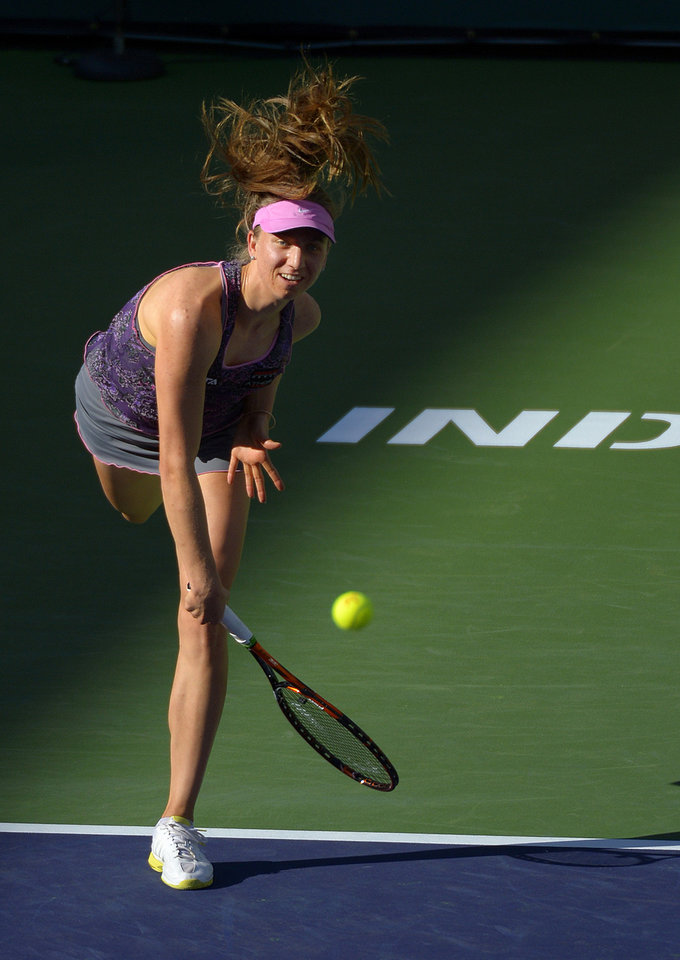 Photo - Mona Barthel, of Germany, serves to Francesca Schiavone, of Italy, during a match at the BNP Paribas Open tennis tournament, Thursday, March 6, 2014, in Indian Wells, Calif. (AP Photo/Mark J. Terrill)