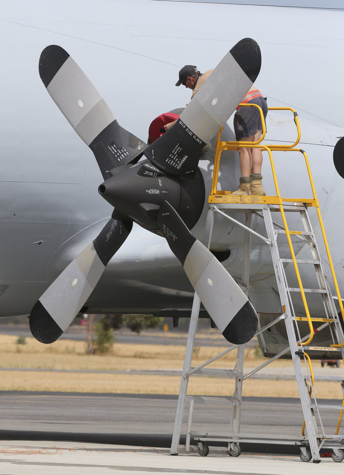 Photo - A ground crew works on a Royal Australian Air Force AP-3C Orion on the tarmac in Perth, Australia, Tuesday, March 25, 2014. All search and rescue flights for the missing Malaysia Airlines flight MH370 were canceled for Tuesday due to bad wether in the search area. (AP Photo/Rob Griffith)