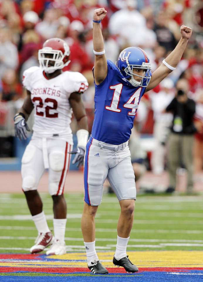 Photo - KU kicker Jacob Branstetter (14) reacts in front of OU's Keenan Clayton (22) after Branstetter made a 57-yard field goal in the second quarter of the college football game between the University of Oklahoma Sooners (OU) and the University of Kansas Jayhawks (KU) on Saturday, Oct. 24, 2009, in Lawrence, Kan. OU won, 35-13. Photo by Nate Billings, The Oklahoman