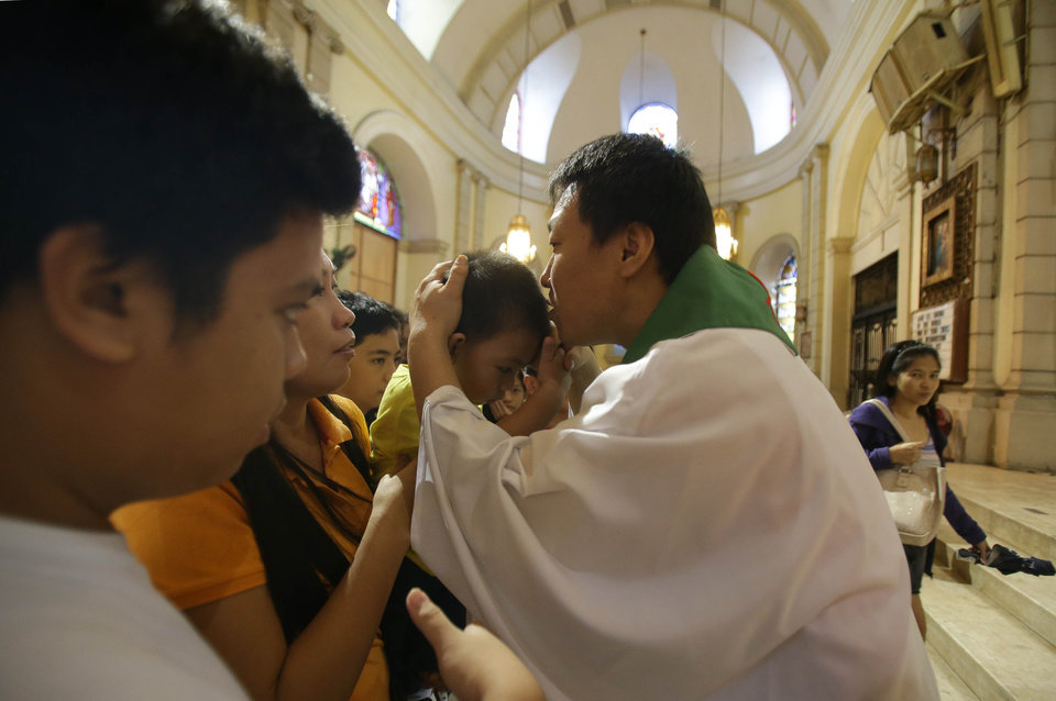 "CORRECTS MONTH - South Korean Catholic priest. Fr. Matthew Park, right, blesses devotees after the mass at the Our Lady of Remedies Parish Church in Manila, Philippines Sunday, Sept. 22, 2013. Catholics around the globe are expressing mixed but mostly positive reactions to Pope Francis' recent remarks that the church has become too focused on ""small minded rules"" on hot-button issues like homosexuality and abortion. (AP Photo/Aaron Favila)"