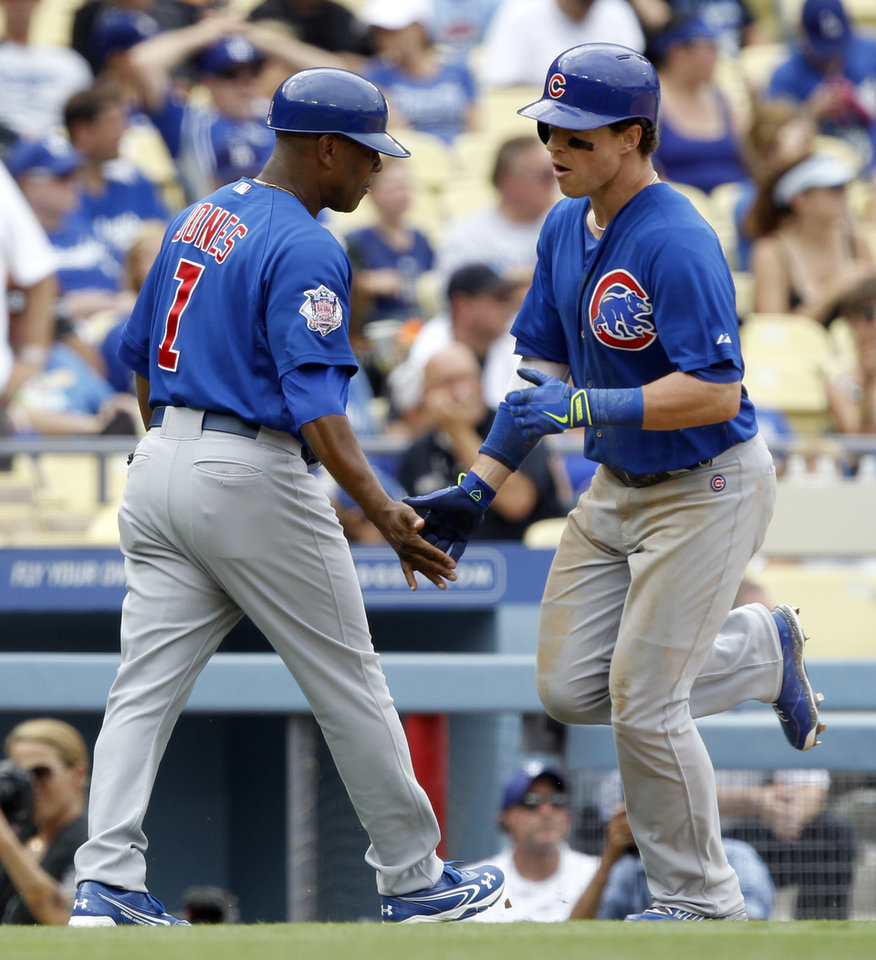 Photo - Chicago Cubs' Chris Coghlan, right, is congratulated by third base coach Gary Jones (1) after he hits a two-run home run in the fifth inning of a baseball game against the Los Angeles Dodgers on Sunday, Aug. 3, 2014, in Los Angeles. (AP Photo/Alex Gallardo)