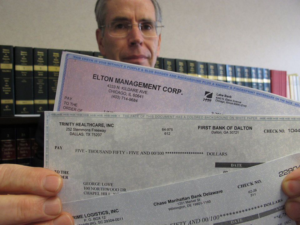 ADVANCE FOR USE SUNDAY, JUNE 24, 2012 AND THEREAFTER - In this Monday, June 11, 2012 photo, Assistant Attorney General David Kirkman holds checks of the type often received by targets in his Raleigh, N.C., office. The recipient forwarded them to his office. Kirkman said sometimes the checks carry the names and account numbers of legitimate companies, and by the time a bank confirms they're bogus, the victim has usually sent the amount to the scammer via wire and ends up on the hook for the money. He also said the amount of money swindled from North Carolinians by these scams has doubled in the past year. (AP Photo/Allen Breed)