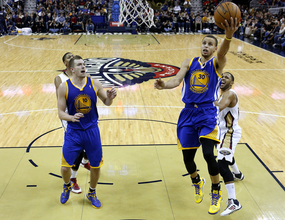 Photo - Golden State Warriors point guard Stephen Curry (30) drives to the basket past New Orleans Pelicans shooting guard Eric Gordon, right, during the second half of an NBA basketball game in New Orleans, Saturday, Jan. 18, 2014. The Warriors won 97-87. (AP Photo/Jonathan Bachman)
