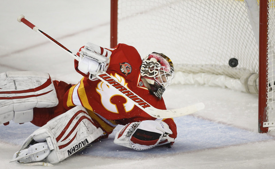 Photo - Calgary Flames goalie Joni Ortio, from Finland, looks back at a goal by the New York Islanders during the second period of an NHL hockey game Friday, March 7, 2014, in Calgary, Alberta. (AP Photo/The Canadian Press, Jeff McIntosh)