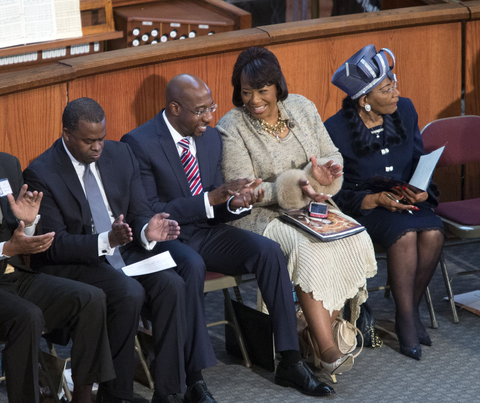 Photo - Bernice King, second from right, talks with pastor Raphael Warnock, second from left, during the Rev. Martin Luther King Jr. holiday commemorative service at Ebenezer Baptist Church Monday, Jan. 20, 2014, in Atlanta. Bernice King is the daughter of the late Dr. Martin Luther King Jr., and Christine King Farris, right, is the only living sibling of the late Dr. Martin Luther King Jr.. Also pictured is Atlanta mayor Kasim Reed, left. (AP Photo/Jason Getz)