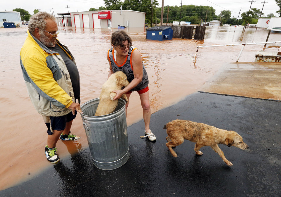 Photo - George and Susan Kruger make one of three trips with their animals from their flooded house to safety on Sunday in Purcell. Water from the overnight rain began to rise early in the morning. The Krugers made several trips to retrieve five dogs and a baby chick.  Photo by Steve Sisney The Oklahoman  STEVE SISNEY -  THE OKLAHOMAN