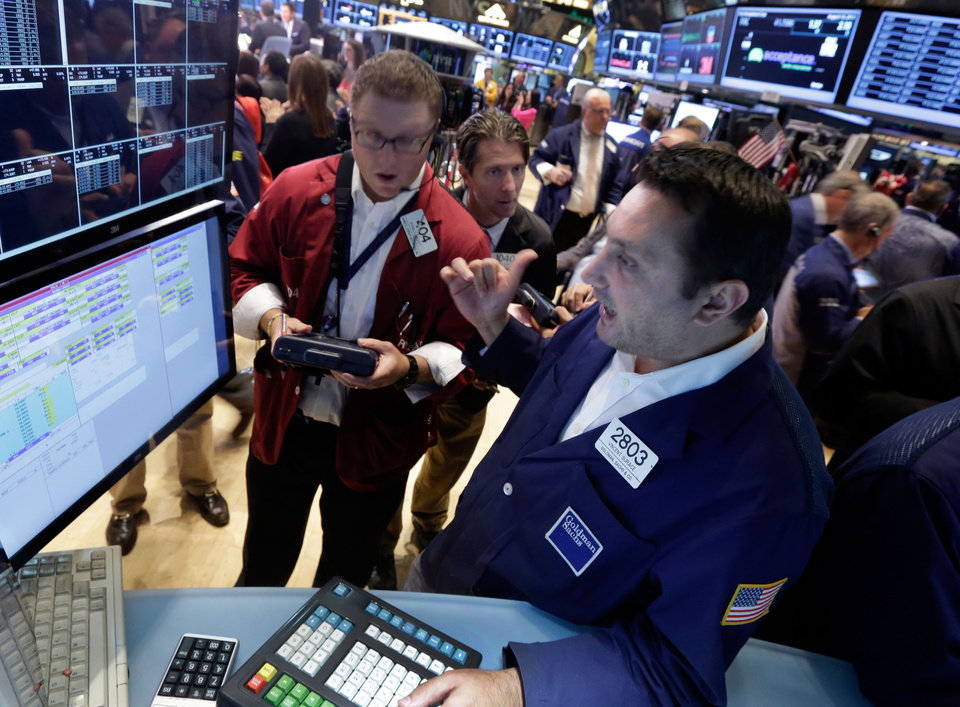 Photo - Specialist Vincent Surace, foreground, works with traders at his post on the floor of the New York Stock Exchange Friday, Aug. 16, 2013. Stocks bounced back Friday from consecutive days of significant declines, with more evidence of a rebounding U.S. housing market. (AP Photo/Richard Drew)