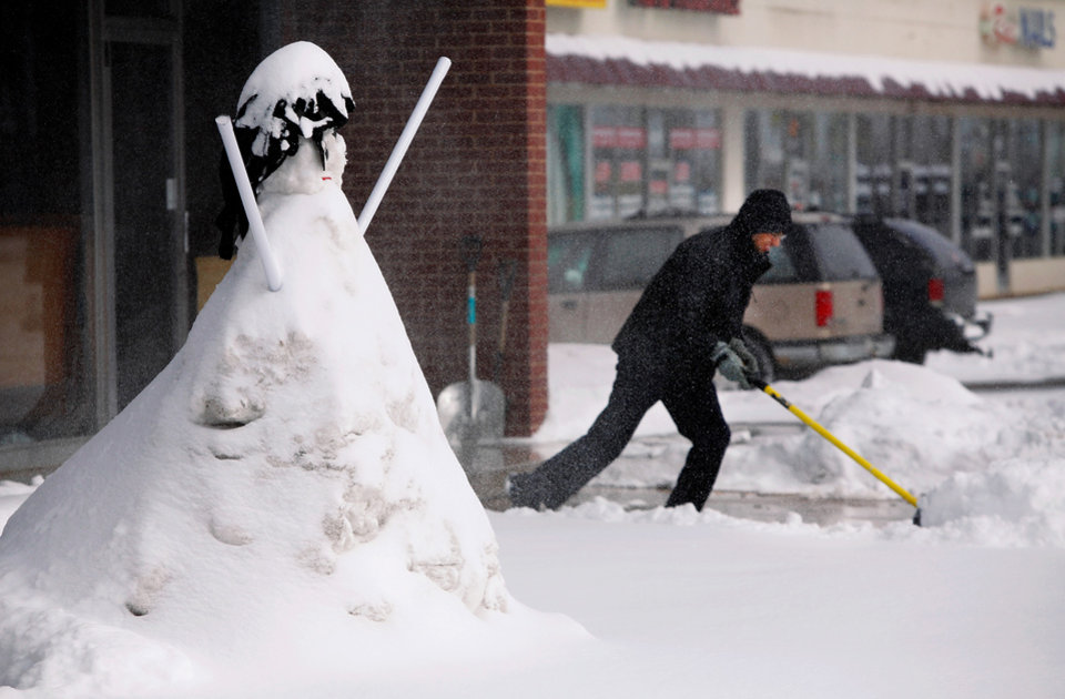 Photo - David Espinosa shovels snow from the parking lot in front of the mattress business he and his brother own on SE 29 Street in Del City. Earlier, his brother, Raul, built this snowman in front of their store. A second winter storm in a week dumped about 6 inches of snow in the Oklahoma City area Tuesday morning, Feb. 9, 2011.   Photo by Jim Beckel, The Oklahoman