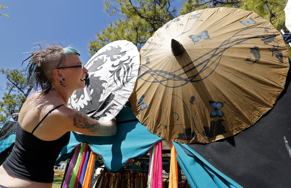 Photo -  Vyla Morell decorates the Starry Dreams Worldly Wares booth on Thursday for the Medieval Fair of Norman. The annual festival in Reaves Park will begin Friday and runs through Sunday.