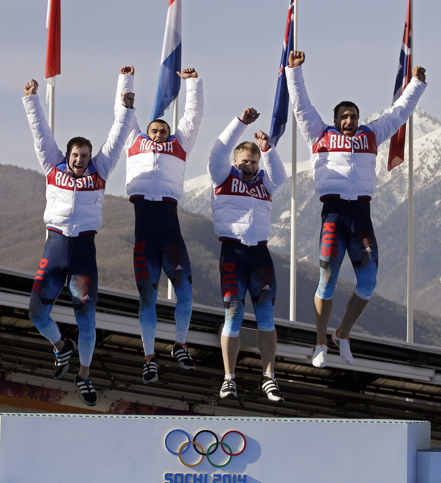 Photo - The team from Russia RUS-1, with Alexander Zubkov, Alexey Negodaylo, Dmitry Trunenkov, and Alexey Voevoda, jump onto the medal stand after they won the gold medal during the men's four-man bobsled competition final at the 2014 Winter Olympics, Sunday, Feb. 23, 2014, in Krasnaya Polyana, Russia. (AP Photo/Michael Sohn)