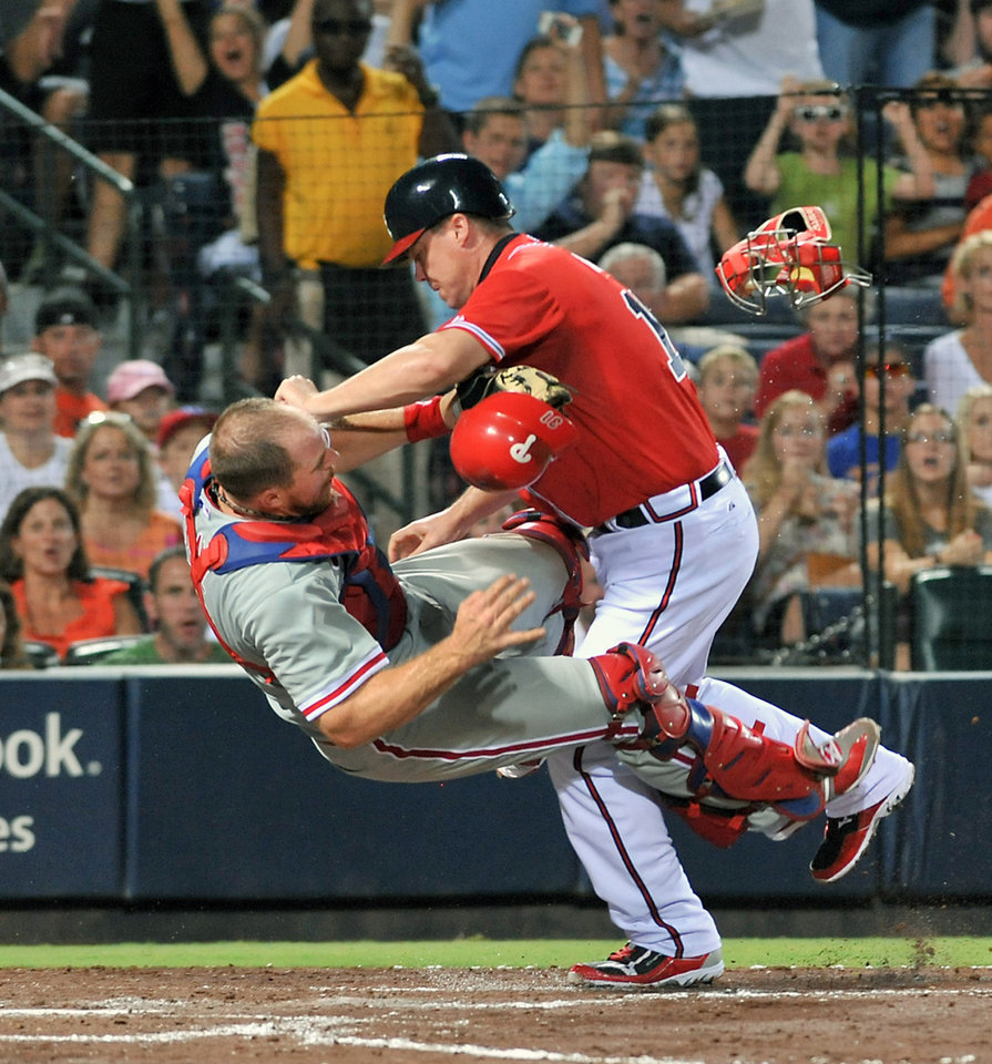 Photo -   Atlanta Braves' Chipper Jones, right, is called out at home plate as he collides with Philadelphia Phillies catcher Erik Kratz, left, during the fourth inning of a baseball game on Friday, Aug. 31, 2012, at Turner Field in Atlanta. (AP Photo/Gregory Smith)