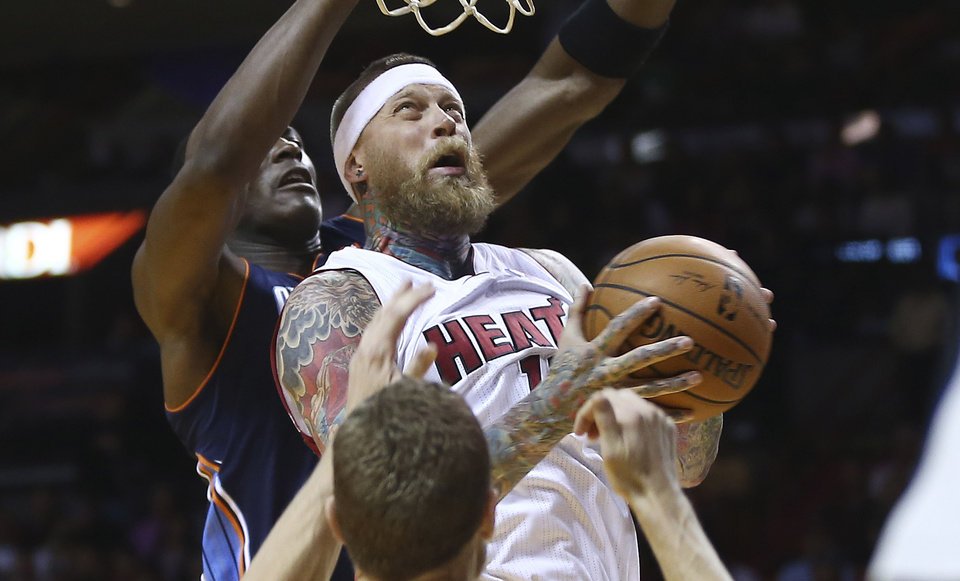 Photo - Charlotte Bobcats' Bismack Biyombo (0) tries to block Miami Heat's Chris Andersen (11) during the first half of an NBA basketball game in Miami, Monday, March 3, 2014. (AP Photo/J Pat Carter)