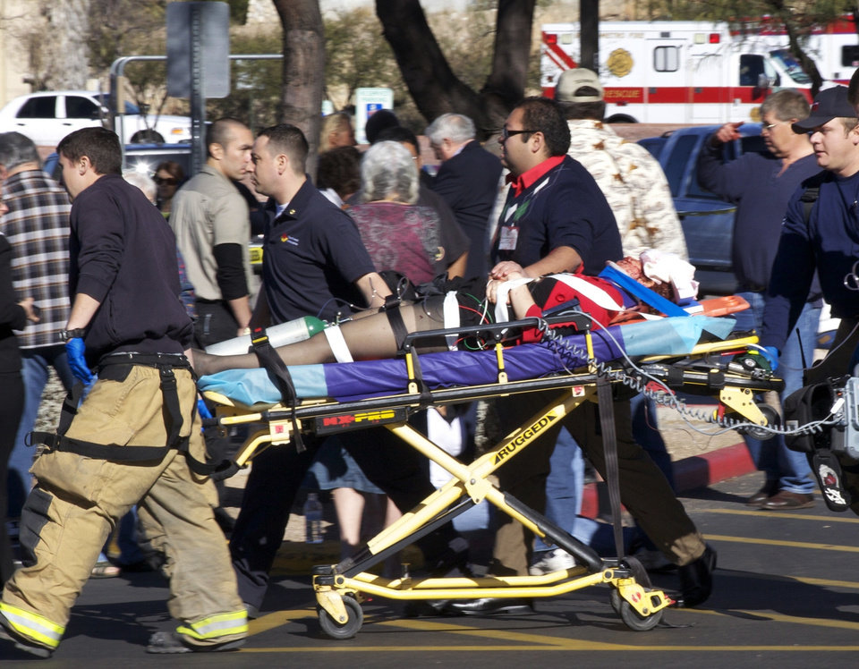 Photo - FILE - In this Jan. 8, 2011 file photo, Emergency personnel and Daniel Hernandez, an intern for U.S. Rep. Gabrielle Giffords, second right, move Giffords after she was shot in the head outside a shopping center in Tucson, Ariz. Hundreds of pages of police reports in the investigation of the shooting rampage were released Wednesday, March 27, 2013 marking the public's first glimpse into documents that authorities have kept private since the attack more than two years ago. (AP Photo/James Palka, File)