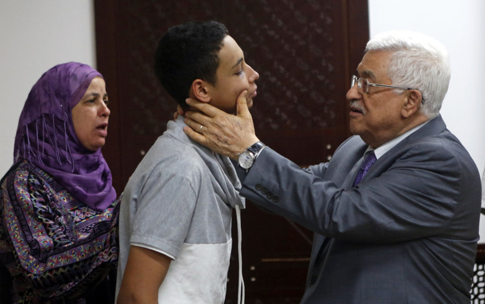 Photo - In this  Monday, July 7, 2014 photo, Palestinian President Mahmoud Abbas, right, checks the injuries of Palestinian-American teen Tariq Abu Khdeir who was beaten by Israeli border police, during a meeting attended by the mother, left, of 16-year-old Mohammed Abu Khdeir who was abducted and burned to death last week in the West Bank town of Ramallah. Three Israeli suspects in the killing of Mohammed who was murdered last week confessed to the crime on Monday and were re-enacting the incident for authorities, an official said, as the country's leaders raced to contain a public uproar over the slaying. (AP Photo/Mohamad Torokman, Pool)