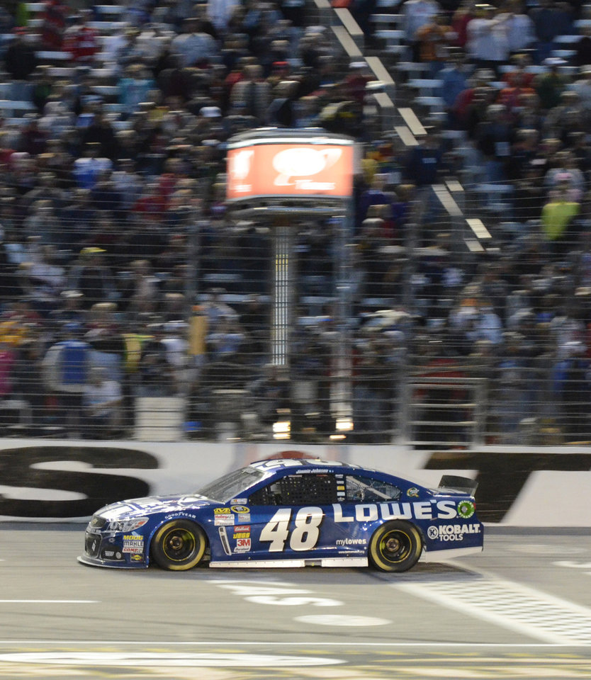 Photo - Jimmie Johnson (48) crosses the finish line winning the NASCAR Sprint Cup series auto race at Texas Motor Speedway in Fort Worth, Texas, Sunday, Nov. 3, 2013. (AP Photo/Larry Papke)