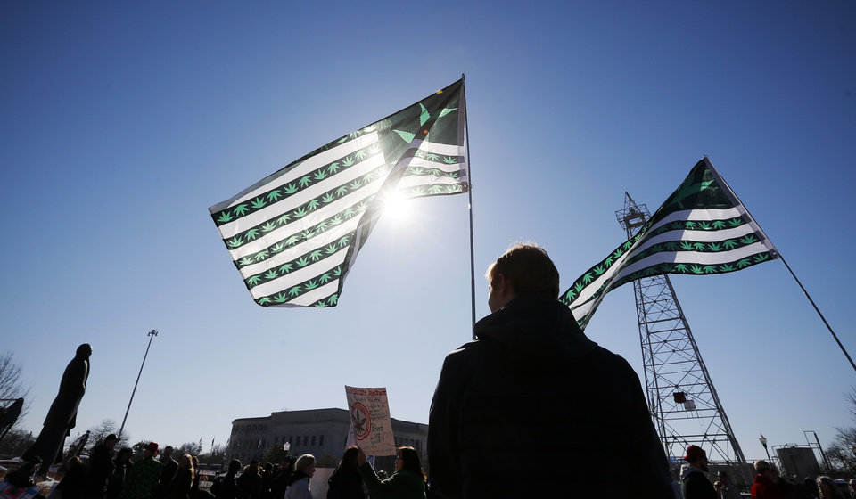 Photo - Julian Kerr of Oklahoma City holds a marijuana flag during March the Capitol 2020 at the state Capitol in Oklahoma City, Thursday, Feb. 6, 2020. The rally was to protest many of the bills filed in the legislative session that would affect medical marijuana patients and businesses. [Nate Billings/The Oklahoman]