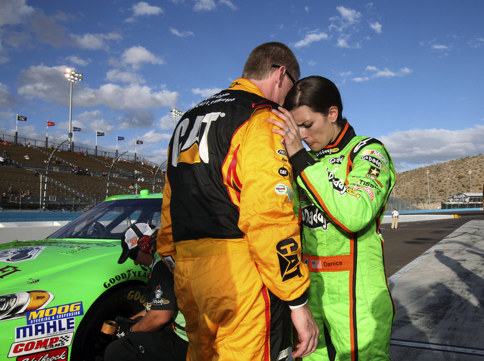 Photo -   Danica Patrick, right, interacts with Jeff Burton, left, following qualifying for the NASCAR Sprint Cup Series auto race, Friday, Nov. 9, 2012, at Phoenix International Raceway in Avondale, Ariz. (AP Photo/Paul Connors)