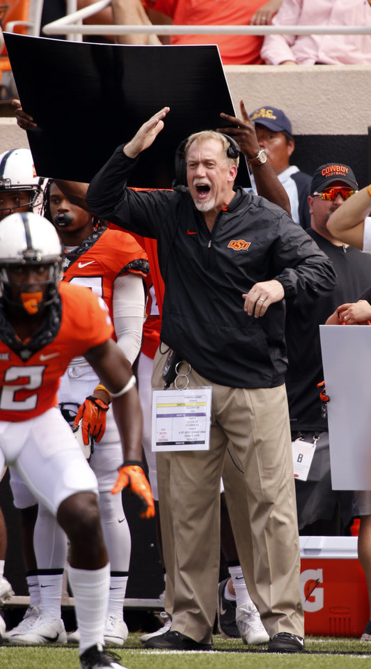 Photo - Defensive coordinator Glenn Spencer signals to the team during the college football game between the Oklahoma State Cowboys (OSU) and the Southeastern Louisiana Lions at Boone Pickens Stadium in Stillwater, Okla., Saturday, Sept. 12, 2015. Photo by Steve Sisney, The Oklahoman