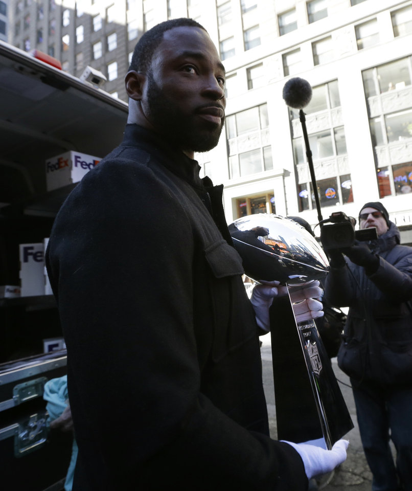 Photo - New York Giants player Justin Tuck holds the Vince Lombardi Trophy after receiving it from a FedEx delivery truck at Times Square to kick off Super Bowl Boulevard Wednesday, Jan. 29, 2014, in New York. The Seattle Seahawks are scheduled to play the Denver Broncos in the NFL Super Bowl XLVIII football game on Sunday, Feb. 2, in East Rutherford, N.J. (AP Photo/Julio Cortez)