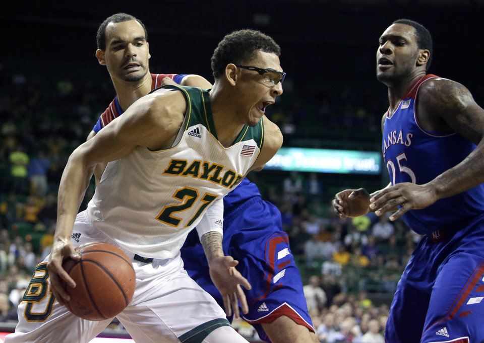 Photo - Baylor center Isaiah Austin (21) looks for an opportunity to go to the basket as Kansas' Perry Ellis, left, and Tarik Black (25) defend in the second half of an NCAA college basketball game, Tuesday, Feb. 4, 2014, in Waco, Texas. Kansas won 69-52. (AP Photo/Tony Gutierrez)