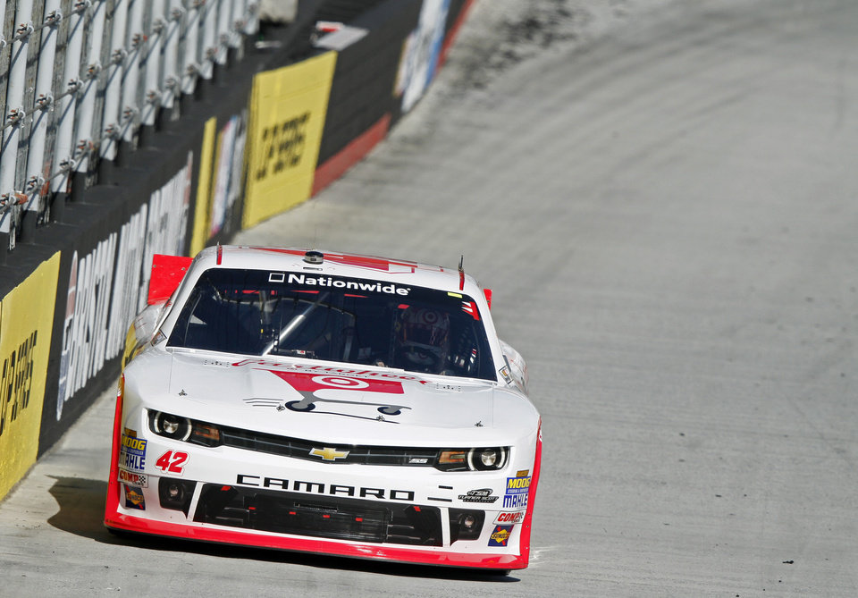 Photo - Driver Kyle Larson (42) makes his way around the track during qualifying for the NASCAR Nationwide series auto race at Bristol Motor Speedway on Saturday, March 15, 2014, in Bristol, Tenn. Larson will start from the pole position. (AP Photo/Wade Payne)