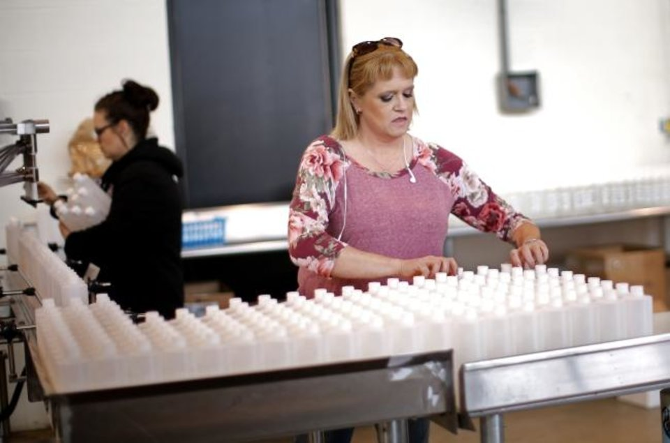 Photo -  Kristy Jones lines up hand sanitizers at Prairie Wolf Vodka in Guthrie on Friday.  [Sarah Phipps/The Oklahoman]