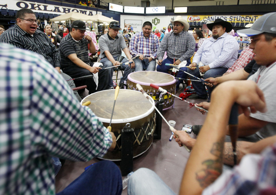 Photo -  Participants in a circle of drummers pound a beat and sing to provide music for dancing at the University of Central Oklahoma's annual powwow. Photo by K.T. King, The Oklahoman   KT King -