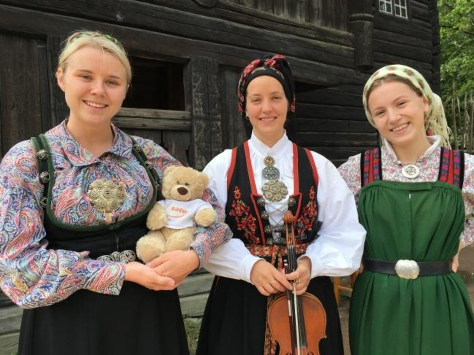 Photo -  Dancers at Oslo's Norsk Folkemuseum pose with Fuzzy, a Society of American Travel Writers traveling teddy who blogs about his adventures for elementary-aged children (teddietravel.blogspot.com). [Elaine Warner Photo]