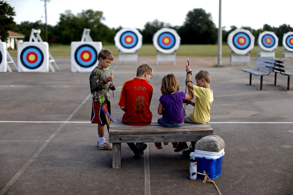 Photo - Children wait to shoot during a Junior Olympic Archery Development Club shoot put on by the Trosper Archery Club on Saturday, August 24, 2013, at Trosper Park in Oklahoma City.  Over 60 participants, from beginners to intermediates, took part in the shoot which takes place every Saturday. For $5 each person is supplied with equipment and instruction starting at 9am for beginners and 10am for intermediate shooters. Photo by Bryan Terry, The Oklahoman