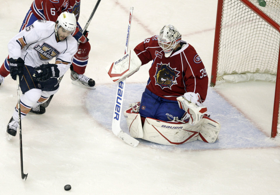 Photo - Oklahoma City's Philippe Cornet attempts a shot on Hamilton goalie Peter Delmas during the AHL hockey game between the Oklahoma City Barons and the Hamilton Bulldogs at the Cox Convention Center in Oklahoma City, Tuesday, April 3, 2012. Photo by Sarah Phipps, The Oklahoman