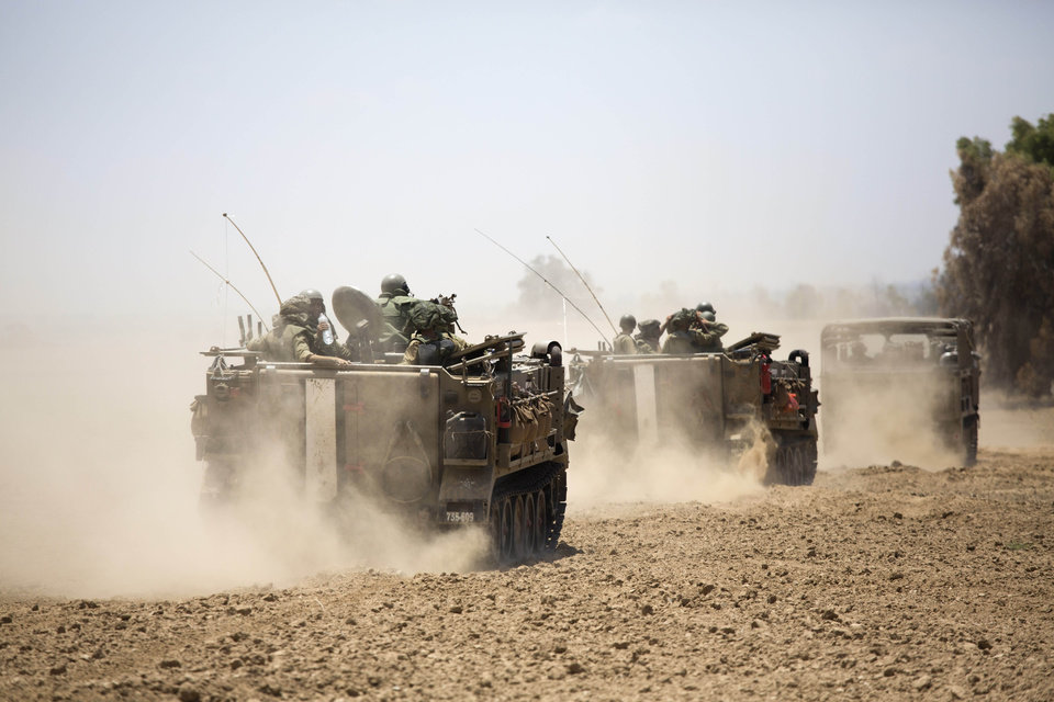 Photo - Israeli armored personnel carriers move along the Israel and Gaza border, Saturday, July 19, 2014. Israel pounded Hamas rocket launchers, uncovered more than a dozen cross-border tunnels and engaged in gunbattles with Palestinian militants Saturday, as fighting intensified on the second day of its open-ended ground operation in Gaza, as the Palestinian death toll continued to rise. (AP Photo/Dusan Vranic)