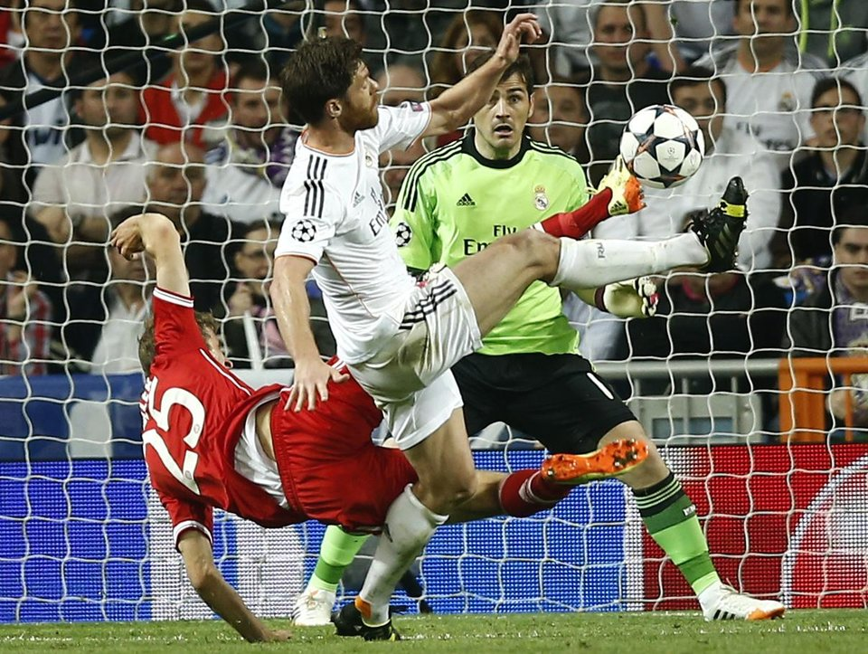 Photo - Bayern's Thomas Mueller fights for the ball with Real's Xabi Alonso during a first leg semifinal Champions League soccer match between Real Madrid and Bayern Munich at the Santiago Bernabeu stadium in Madrid, Spain, Wednesday, April 23, 2014. (AP Photo/Andres Kudacki)