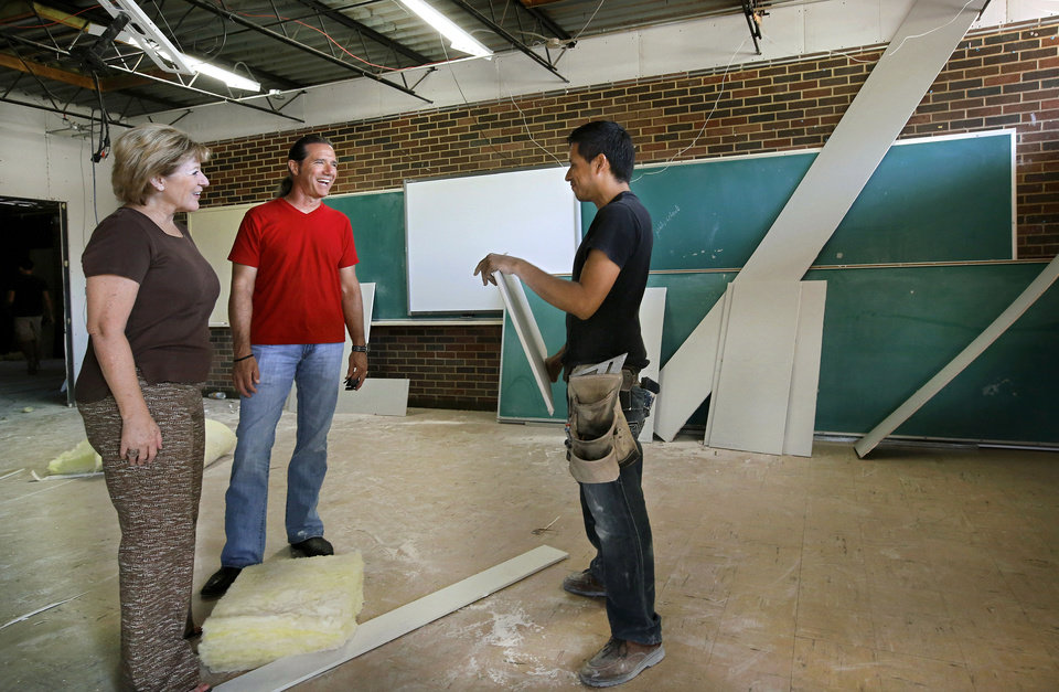 Photo - Pam Westbrook, left, human resources consultant, and Jimi Fleming, center, communications  liason,  talk to  Misael Ibarra, a Hutchco Construction employee. Workers are converting rooms at  Central Junior High School in Moore  for elementary students  displaced by the May 20 tornado.   Photo  by Jim Beckel, The Oklahoman.  Jim Beckel - THE OKLAHOMAN