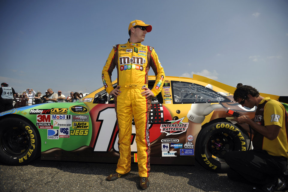 Photo -   NASCAR driver Kyle Busch stands next to his car following his qualifying attempt at Talladega Superspeedway in Talladega, Ala., Saturday, Oct. 6, 2012. The drivers were qualifying for the Sunday running of the NASCAR Sprint Cup Series auto race. (AP Photo/Rainier Ehrhardt)