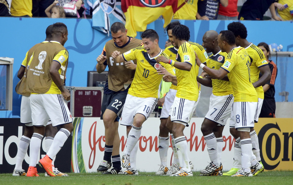 Photo - Colombia's James Rodriguez (10) celebrates with his teammates after scoring the opening goal during the group C World Cup soccer match between Colombia and Ivory Coast at the Estadio Nacional in Brasilia, Brazil, Thursday, June 19, 2014.  (AP Photo/Sergei Grits)