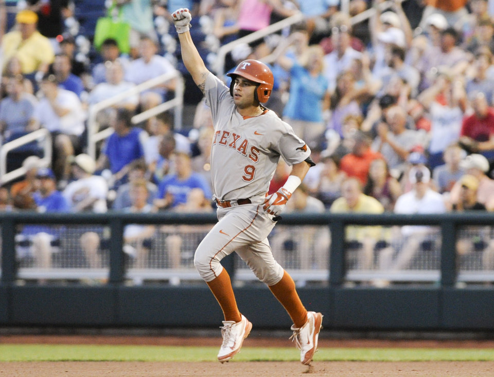 Photo - Texas' C.J Hinojosa (9) raises his fist as he rounds the bases after hitting a solo home run against UC Irvine in the seventh inning of an NCAA baseball College World Series elimination game in Omaha, Neb., Wednesday, June 18, 2014. (AP Photo/Eric Francis)