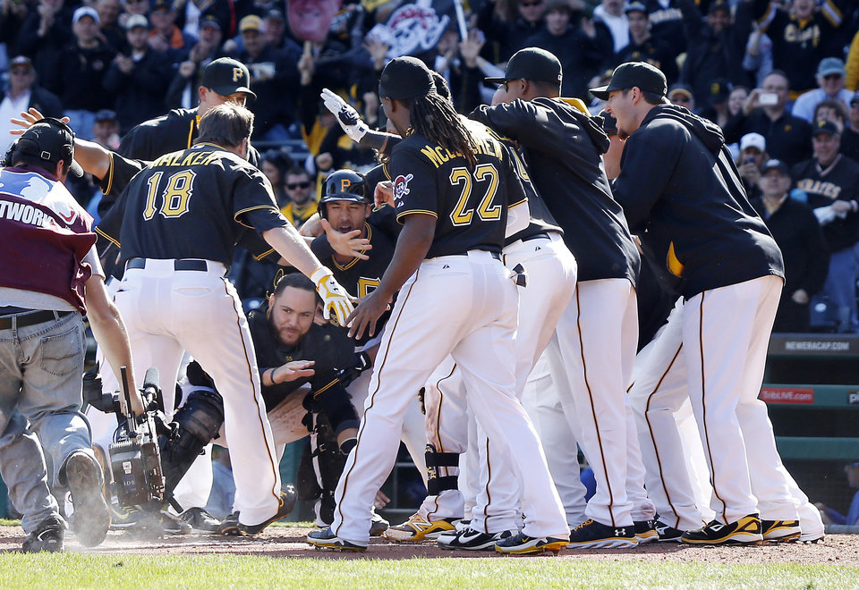 Photo - The Pittsburgh Pirates circle home plate as they wait for Neil Walker (18) to tag the plate after he hit a game-winning home run in the tenth inning of an opening day baseball game against the Chicago Cubs on Monday, March 31, 2014, in Pittsburgh. The Pirates won 1-0 in ten innings. (AP Photo/Keith Srakocic)