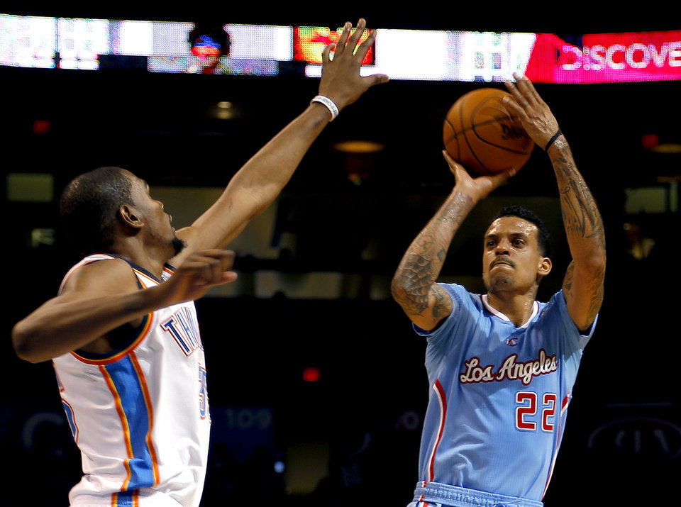 Photo - Los Angeles' Matt Barnes (22) shoots over Oklahoma City 's Kevin Durant (35) during the NBA game between the Oklahoma City Thunder and the Los  Angeles Clippers at the Chesapeake Energy Arena, Sunday, Feb. 23, 2014. Photo by Sarah Phipps, The Oklahoman